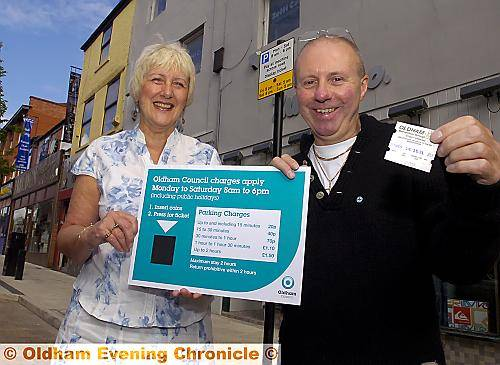 PARKING prices plummet . . . Councillor Lynne Thompson and Zutti owner Paul Hughes with the new sign showing reduced on-street parking prices in Oldham town centre