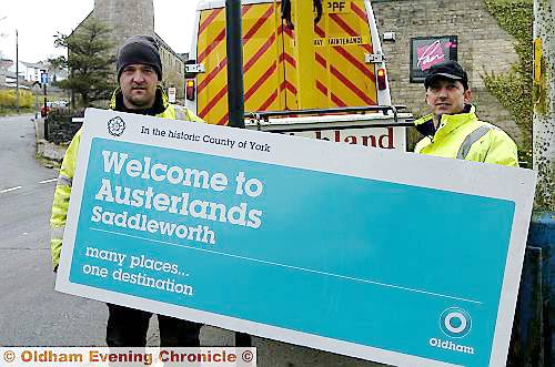 Anthony Briars (left) and Gary Clare, putting up the new Oldham Council sign welcoming visitors to Austerlands