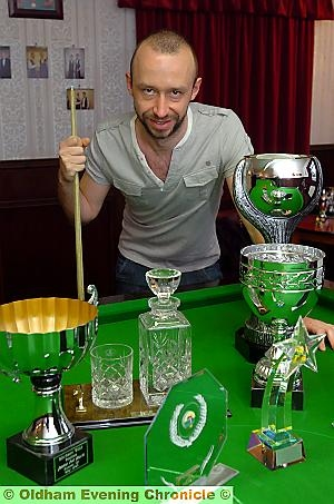 BAIZE OF GLORY . . . Michael shows off the many trophies in his Moorside snooker room.