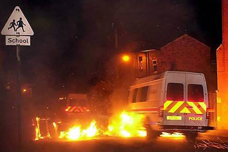 police vans drive through flames in the early hours as gangs of youths hurled petrol bombs at officers and erected burning barricades on the riots' second night