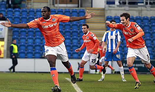 plenty to smile about . . . Jean-Yves Mvoto wheels away after putting Athletic in front at Colchester.