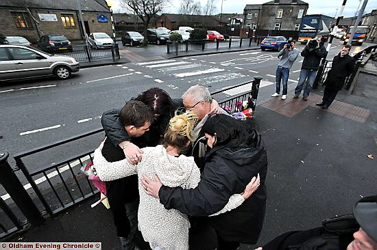 HEARTACHE . . . the family after laying flowers at the scene