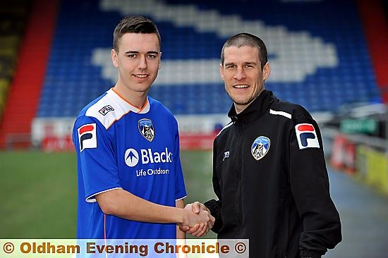 WELCOME ABOARD . . . striker Rhys Turner shakes hands with Athletic first-team coach Paul Murray after signing today