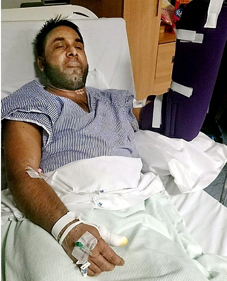 ATTACKED . . . injured driver Ashiq Pervaz lies in his hospital bed