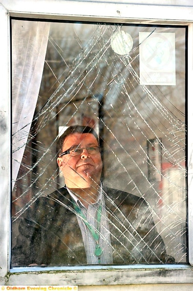 COUNTING the cost: Oldham RL chairman Chris Hamilton looks through a broken window after the latest attack.