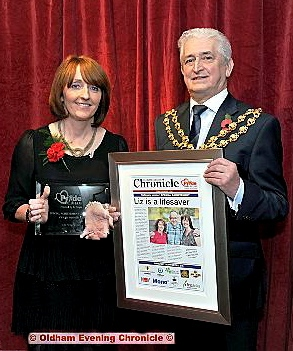 Proud: last year�s Special Achievement Award winner Liz Whitworth is presented with her trophy and framed front page by Oldham Mayor, Councillor John Hudson