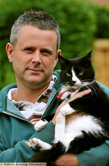 WARNING to pet owners . . . Jon Baylis and his cat George, who was caught in a snare.