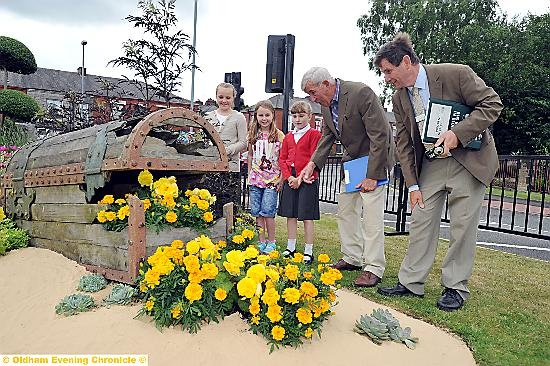 Judges Roger Burnett (right) and Jim Buttress at the underwater themed legacy bed at Broadway junction on Rochdale Road. Children from St Anne's School in Royton helped plant some of the flowers. From the left: Teigan Wheeler, Heidi Burton and Ashleigh Bowskill.