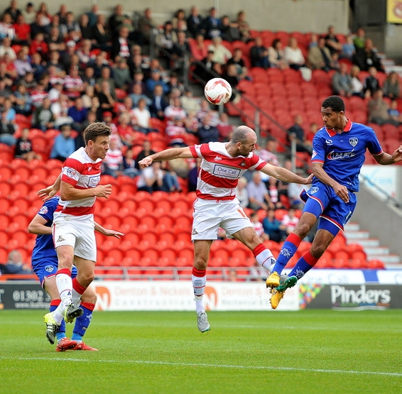 HIGH FLIER: Timothee Dieng leaps above the Doncaster defence to power a header towards goal.