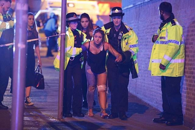 An injured girl is led away by police to a waiting ambulance after the concert explosion