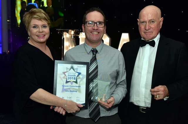 John Mushing, a porter at the Royal Oldham's pharmacy department (centre), receives his Patients' Choice Award