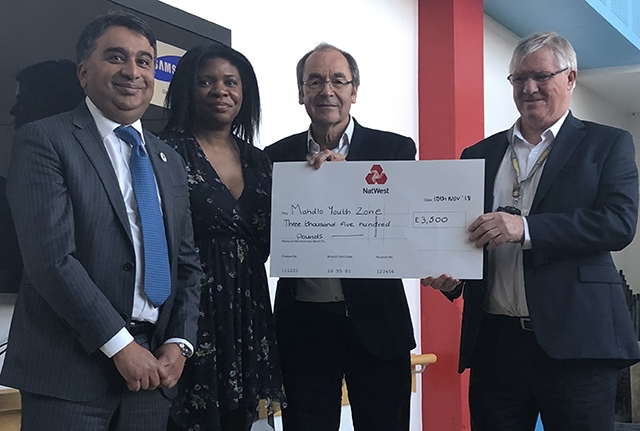 Oldham Business Awards steering group members Kashif Ashraf, Dawn Torrington and Martyn Torr present a cheque to Mike Doran (right), chief executive of Mahdlo