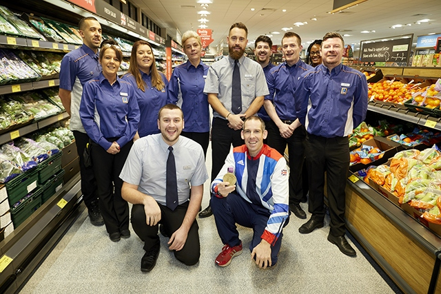 Etienne Stott MBE with the staff at the refurbished Aldi store