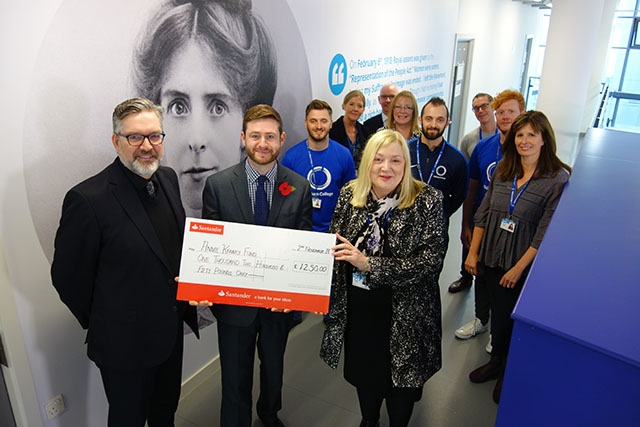 Oldham College students and staff hand over a £1,250 cheque to MP Jim McMahon