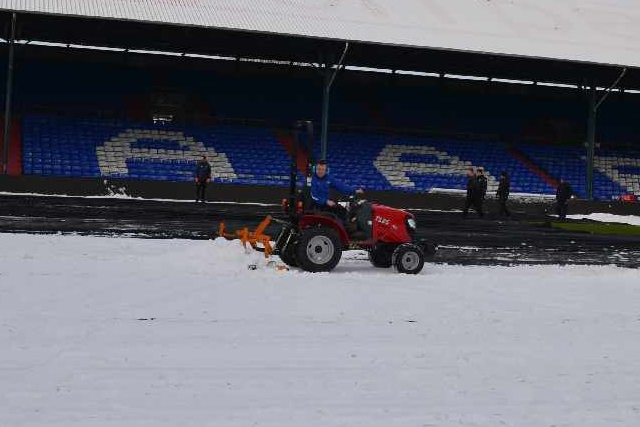 Staff and supporters help clear the snow at Boundary Park
