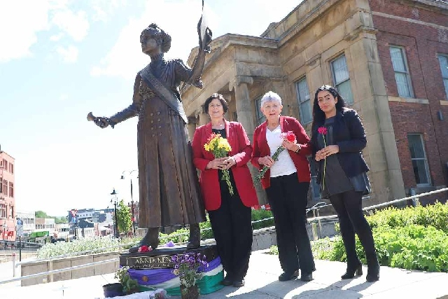 (L-R) Councillors Ginny Alexander, Jenny Harrison and Arooj Shah meeting at the Annie Kenney statue in Oldham town centre earlier today (May 21).
