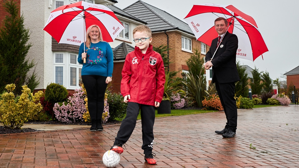 Charlie Kearney from Springhead AFC poses in his new kit funded by Redrow, with mum Felicity Kearney & Redrow's Michael Deegan