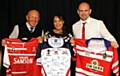 GETTING SHIRTY: Neil Roden (right) shows off auction items alongside his wife, Tanya, and MC Jack Dearden. Picture: Dave Murgatroyd
