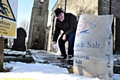 Brian Devenport Deputy Church Warden at The Church of St. Anne, Lydgate spreads salt on the church path.