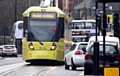 Two trams were halted for 20 minutes when the driver of a car refused to move.