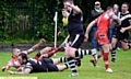OVER WE GO . . . James Whalley dives in to put Saddleworth Rangers ahead against Kells