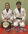 A NAME TO REMEMBER . . . 12-year-old prospect Libby Genge is pictured with her coach Sophie Cox and their judo and Brazilian jiu jitsu medals