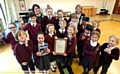 OUTSTANDING . . . head teacher Elizabeth Travis (back left), deputy head Deborah Hodgin (back right) and pupils show off the letter from Schools Minister Nick Gibb