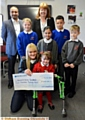MAKING a wish come true . . . Olivia Berry and mum Christie Kindon receive the donation. Back, from left, Rais Bhatti (head of school, Yew Tree), Eleanor Riley (Mather Street), Sally Brown (head of school Mather Street), Hannah Ahmed (Yew Tree), Nico O�Reilly (Mather Street) and Liam Vickery (Yew Tree)