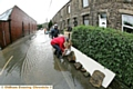 STEM the tide: residents battle against the elements in Delph New Road, Delph, as the floods threaten to take hold