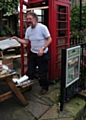 PAUL CLEGG reglazing a phone box - the defib's new home