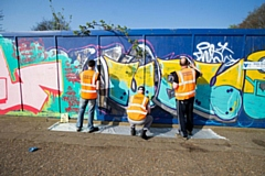 Doing their bit: Offenders clearing graffiti from a wall
