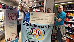Pictured receiving their cheques from Coop store staff members, Louie Daley, Sophie Ball, Wendy Johnson and Martin Poole are Adrian Green, Stephen Hewitt and Scott Longley from the Saddleworth Village Olympics.