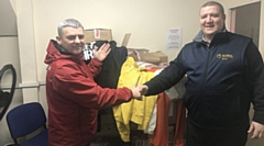 Marcel Duffy (right) hands over the tops and track suits