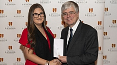 Liberty Kwai Wilcox is pictured receiving an award from Professor Iwan Davies, Vice-Chancellor of Bangor University
