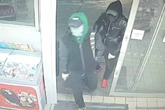 The two men are wanted in connection with the robbery at a petrol station in Oldham