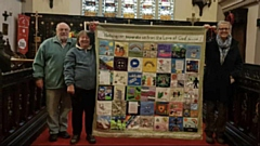 Janet is pictured with the banner, her husband Geoff and Canon Jones