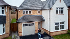 Megan Jones and Phil McGrath with son Harley outside their new home at Saddleworth View