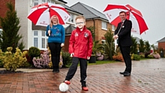 Charlie Kearney from Springhead AFC poses in his new kit funded by Redrow, with mum Felicity Kearney and Redrow sales consultant Michael Deegan at Saddleworth View (photo taken pre-national lockdown)